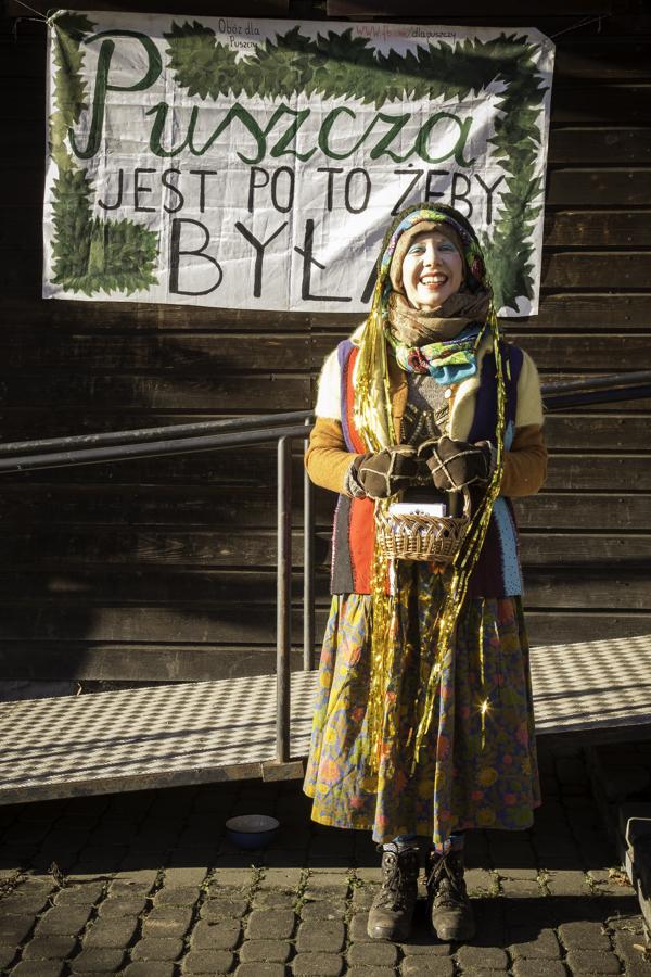 Baba (Anna Błachno) pod budynkiem starej szkoły w Teremiskach na tle napisu Puszcza jest po to, żeby była.