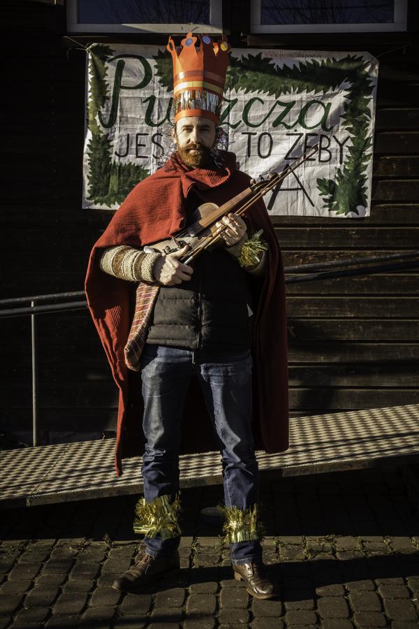 Król/Mędrzec (Mateusz Niwiński) pod budynkiem starej szkoły w Teremiskach na tle napisu Puszcza jest po to, żeby była.