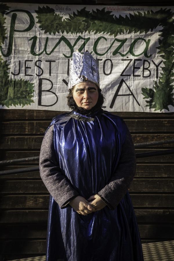 Król/Mędrzec (Julita Charytoniuk) pod budynkiem starej szkoły w Teremiskach na tle napisu Puszcza jest po to, żeby była.
