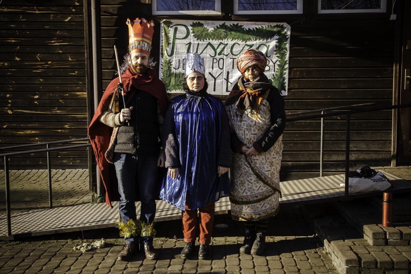 Trzej Królowie/Mędrcy (od lewej: Mateusz Niwiński, Julita Charytoniuk, Zuza Marszewska) pod budynkiem starej szkoły w Teremiskach na tle napisu Puszcza jest po to, żeby była.