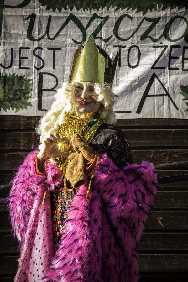 Królowa (Kasia Paterek) pod budynkiem starej szkoły w Teremiskach na tle napisu Puszcza jest po to, żeby była.