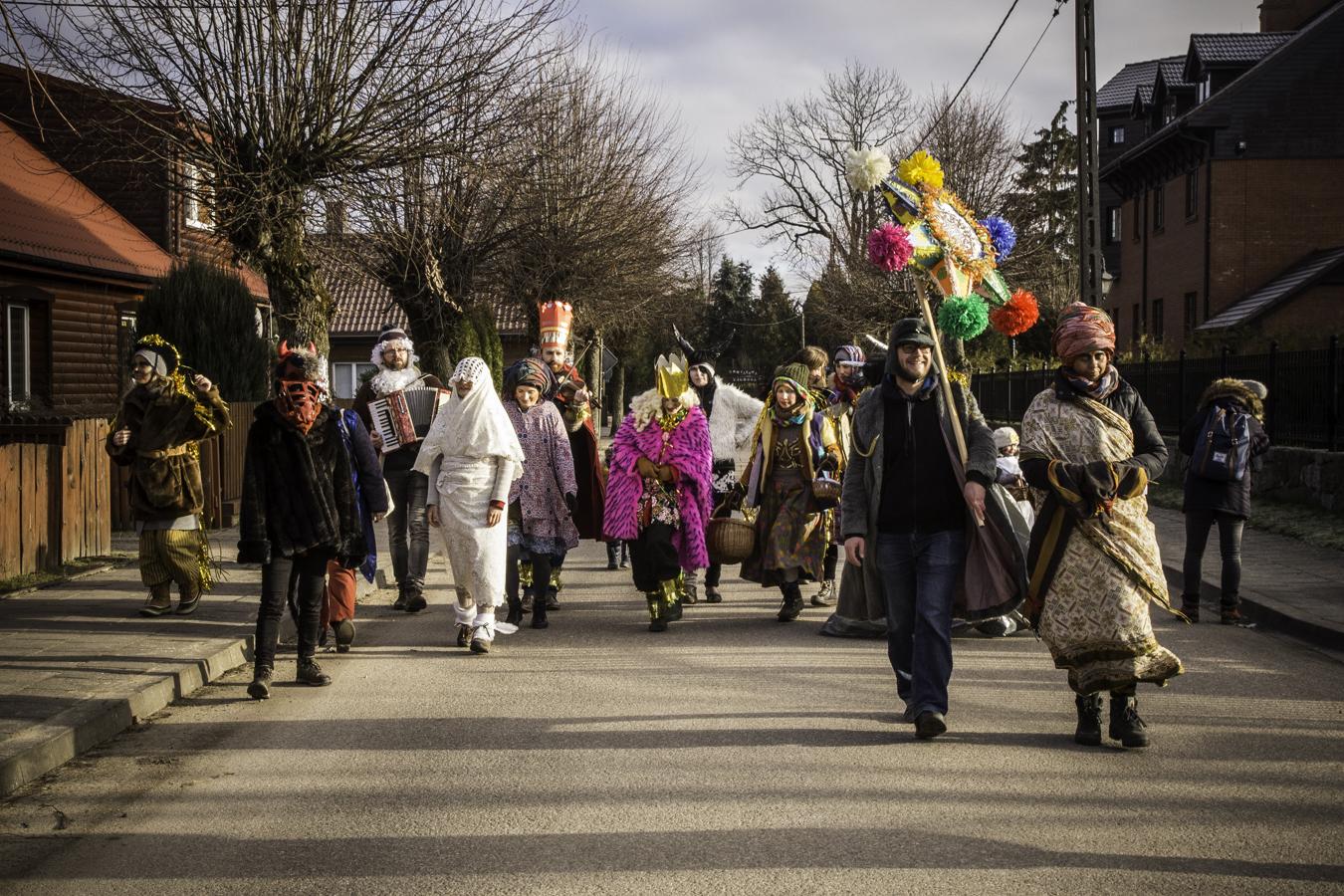Kolędnicy idą ulicą Białowieży ze śpiewem i muzyką.