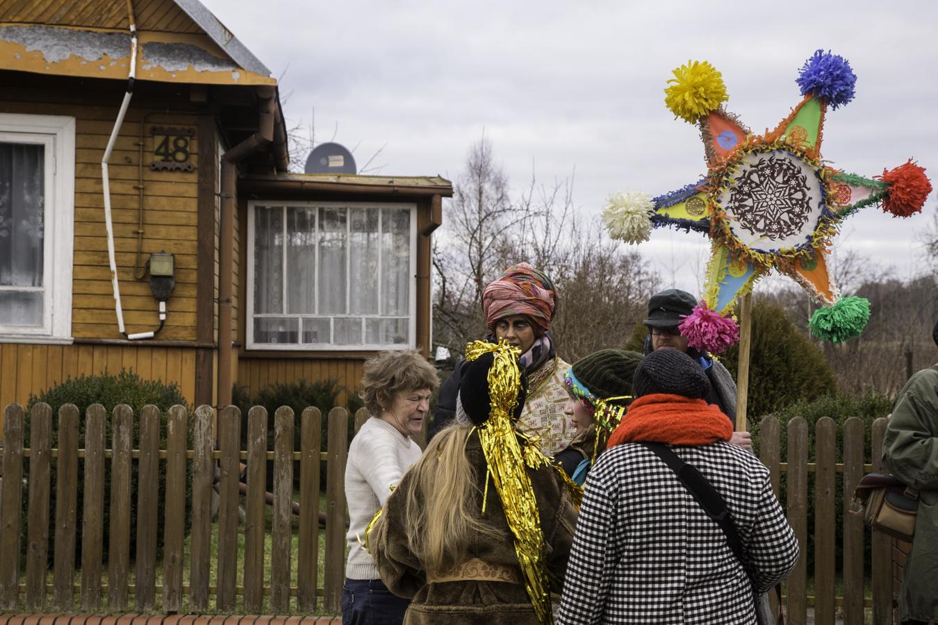 Spotkanie na ulicy Białowieży. Gospodyni wybiegła za kolędnikami, obawiając się pominięcia swojego domu.