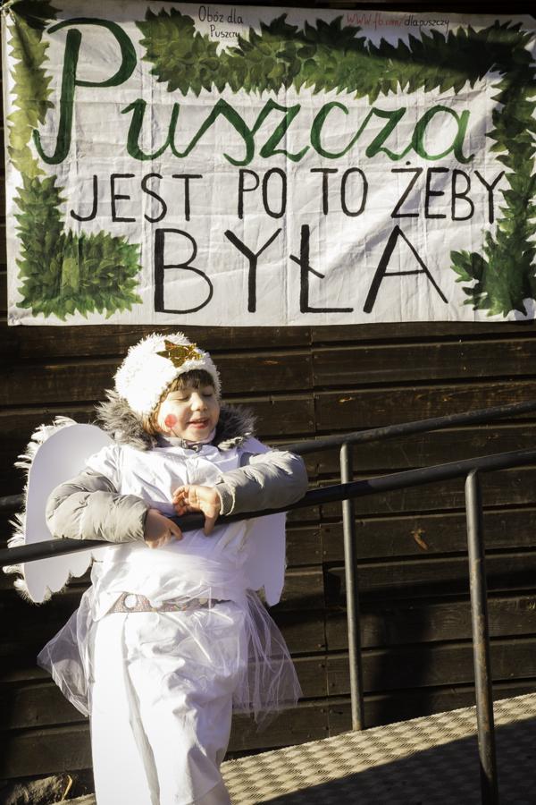 Anioł pod budynkiem starej szkoły w Teremiskach na tle napisu Puszcza jest po to, żeby była.