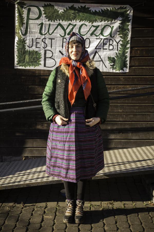 Baba (Agnieszka Zawadka) pod budynkiem starej szkoły w Teremiskach na tle napisu Puszcza jest po to, żeby była.